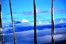 View of prayer flags with playful floating clouds at the distance through Scott lens.