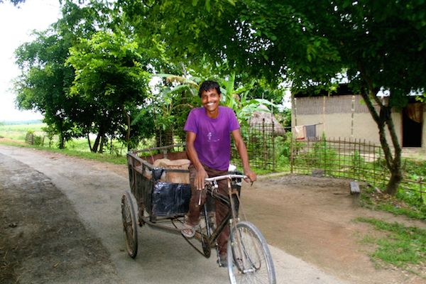 Three tyre manual cart being pulled by man yet wearing smile regardless of scorching heat at periphery of Kaziranga National Park.